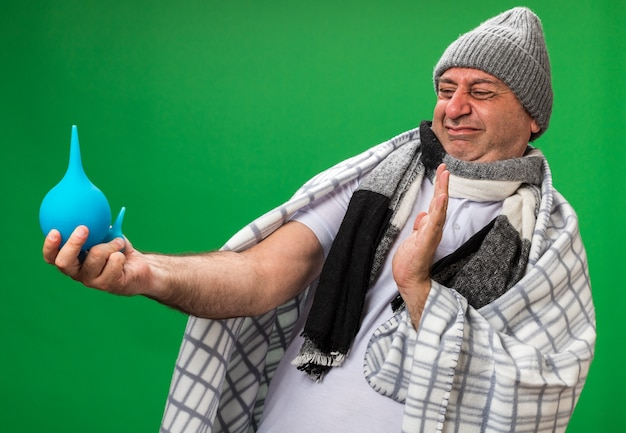 Annoyed adult ill caucasian man with scarf around neck wearing winter hat wrapped in plaid holding and looking at enemas isolated on green wall with copy space