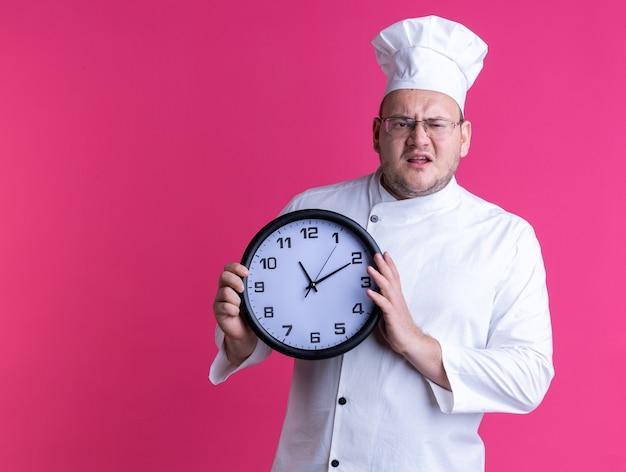 Infastidito maschio adulto cuoco indossando l'uniforme dello chef e occhiali tenendo l'orologio guardando la parte anteriore isolata sulla parete rosa con spazio di copia