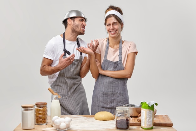 Annoyed adult man looks angrily at wife, asks to stop cooking, feels tired of making dough, cheerful woman in apron enjoys hobby and making delicious pastry. culinary and baking during quarantine