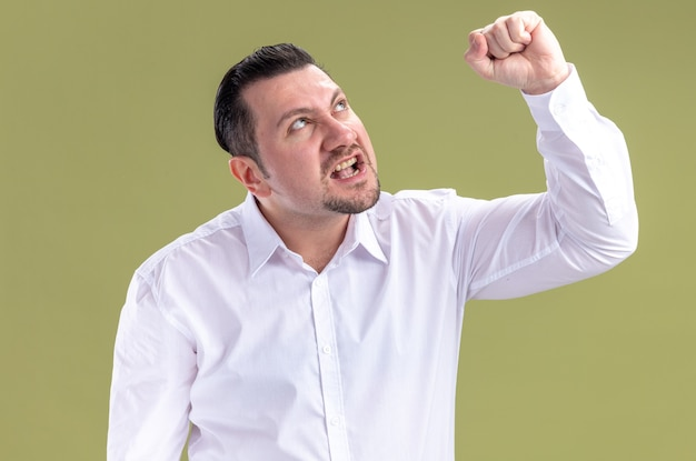 Annoyed adult slavic businessman raising fist and looking up