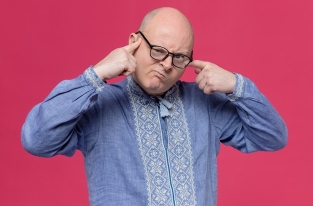 Раздраженный взрослый славянский мужчина в синей рубашке в оптических очках кладет пальцы на лицо