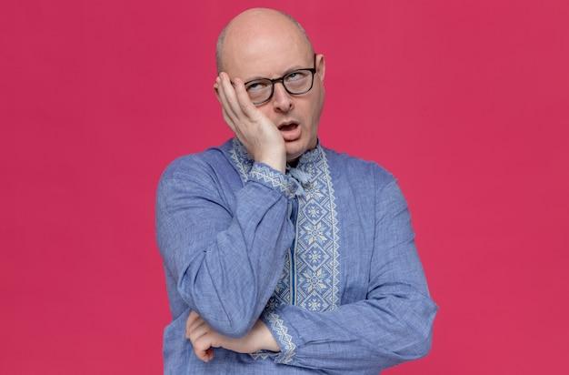 彼の顔に手を置き、目を転がしている光学眼鏡をかけている青いシャツを着たイライラした大人のスラブ人