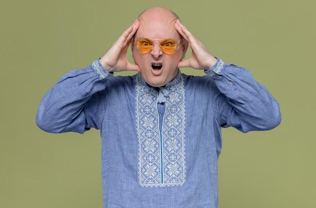 彼の頭を保持しているサングラスを身に着けている青いシャツのイライラした大人のスラブ人