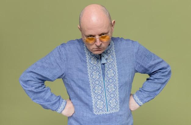 파란색 셔츠를 입은 성가신 성인 슬라브 남자는 선글라스를 끼고 허리에 주먹을 얹고