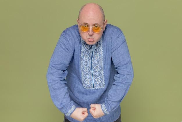 선글라스를 끼고 어깨를 들어올리고 주먹을 꽉 쥐고 있는 파란 셔츠를 입은 성가신 성인 슬라브 남자