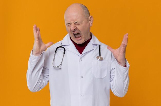 Раздраженный взрослый славянский мужчина в медицинской форме со стетоскопом держит руки открытыми и кричит
