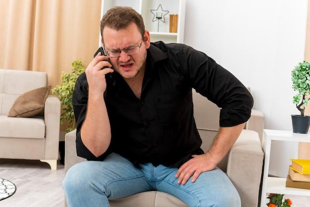 光学ガラスのイライラした大人のスラブ人は、リビングルーム内の電話で話している肘掛け椅子に座っています