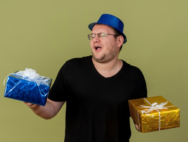 Annoyed adult slavic man in optical glasses wearing blue party hat holds gift boxes