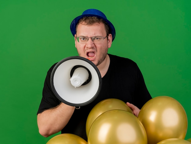 Annoyed adult slavic man in optical glasses wearing blue party hat holds helium balloons and shouts into loud speaker