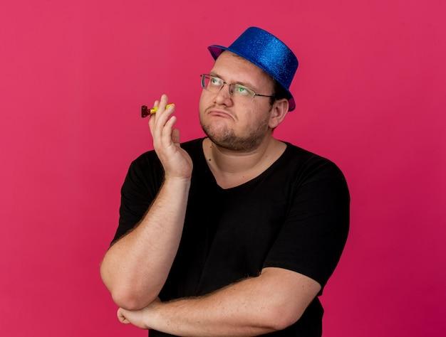 L'uomo slavo adulto infastidito con gli occhiali ottici che indossa un cappello da festa blu tiene un fischio di festa