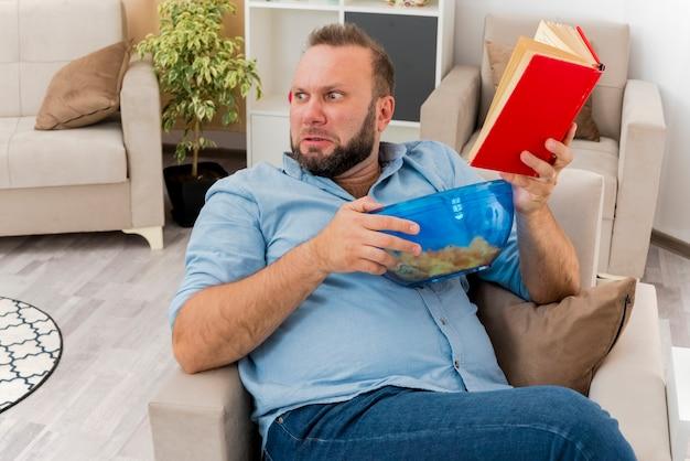 Uomo slavo adulto infastidito si siede sulla poltrona che tiene una ciotola di patatine e libro guardando a lato all'interno del soggiorno