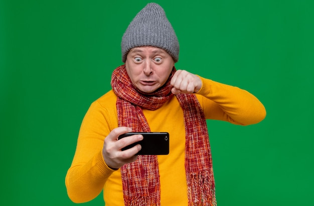 Annoyed adult slavic man with winter hat and scarf around his neck holding phone and keeping fist