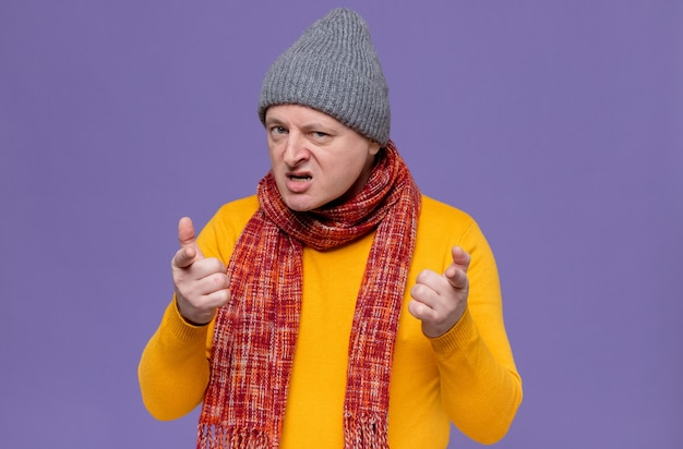 Annoyed adult slavic man with winter hat and scarf around his neck looking and pointing at camera