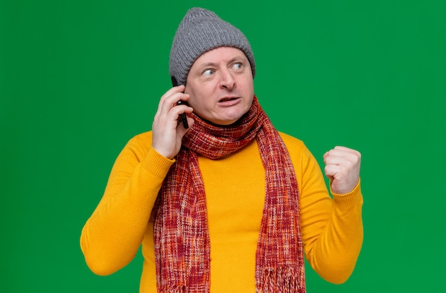 Annoyed adult slavic man with winter hat and scarf around his neck talking on phone and keeping fist looking at side