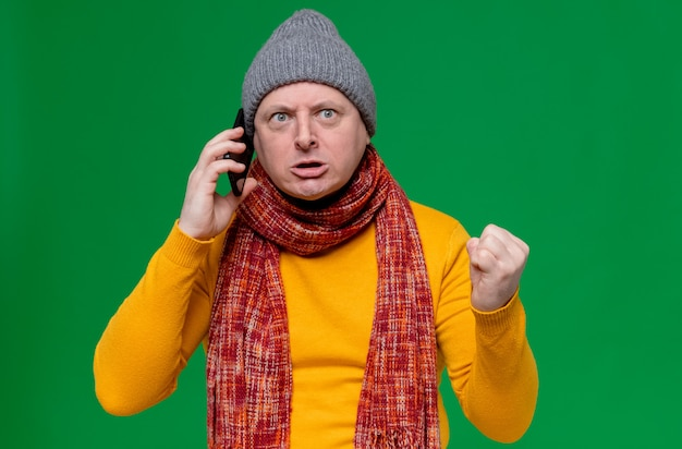 Annoyed adult slavic man with winter hat and scarf around his neck talking on phone and keeping fist