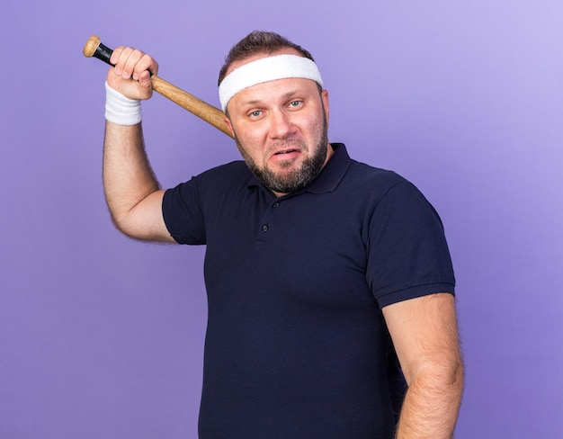 Раздраженный взрослый славянский спортивный мужчина с головной повязкой и браслетами, держащий летучую мышь на плече, изолированный на фиолетовой стене с копией пространства
