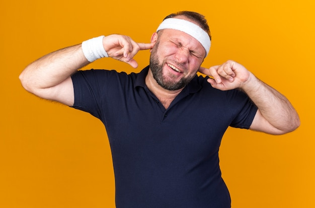 Annoyed adult slavic sporty man wearing headband and wristbands closing his ears with fingers isolated on orange wall with copy space