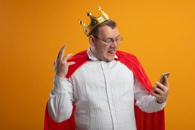 Uomo adulto infastidito del supereroe slavo in mantello rosso con gli occhiali e corona che tiene e guardando il telefono cellulare tenendo la mano in aria isolata sulla parete arancione con lo spazio della copia