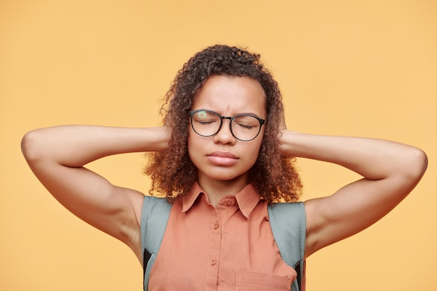 Annoyed african-american student girl in eyeglasses keeping eyes closed and covering ears to not listen, yellow background