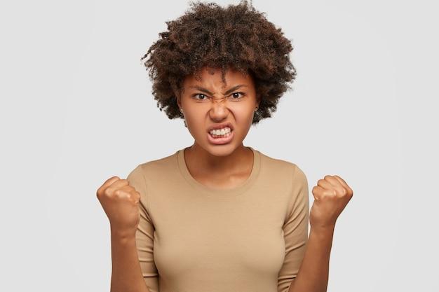 La donna afroamericana infastidita stringe denti e pugni, essendo irritata