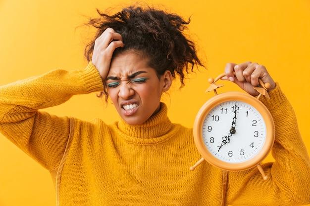 孤立して立っているセーターを着て、目覚まし時計を保持しているイライラするアフリカの女性