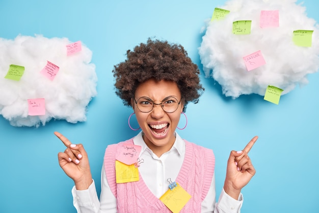 La donna afroamericana infastidita esclama negativamente indica sopra sulle nuvole con note adesive esprime emozioni negative indossa occhiali rotondi vestiti puliti isolati sopra il muro blu dello studio