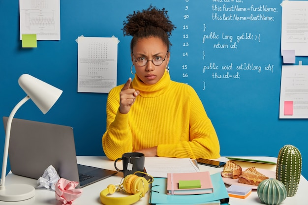 Annoyed afro american woman worker points at you and blames in doing something wrong, wears round glasses and yellow jumper, sits in coworking space with mess on table.
