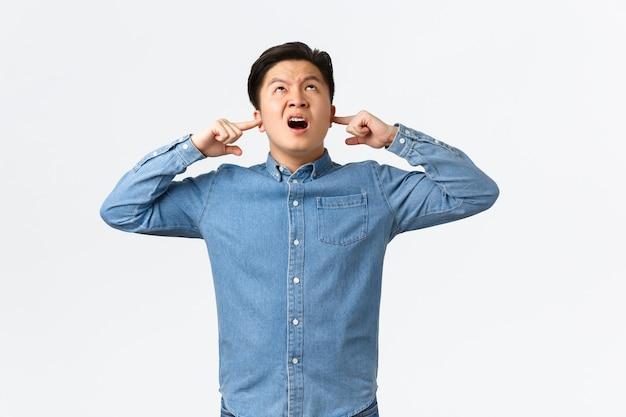 짜증나고 성가신 아시아 남성은 시끄러운 이웃에 대해 불평하고, 손가락으로 귀를 막고, 불쾌한 표정을 짓고, 위층에 있는 사람들에게 소리를 지르고, 성가신 음악을 끄고, 흰색 배경에 서 있습니다.