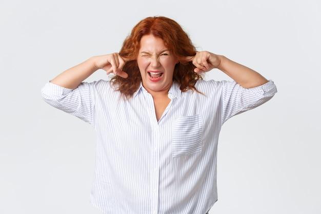 Раздраженная и обеспокоенная, жалующаяся, рыжая женщина средних лет гримасничает и закрывает уши пальцами от ужасного назойливого шума, терпеть не может громкую ужасную музыку, стоит белая стена.