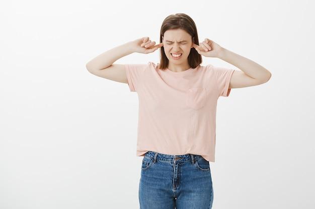 イライラして悩む女子学生が耳を閉じ、大きな音や邪魔な音から何も聞こえない