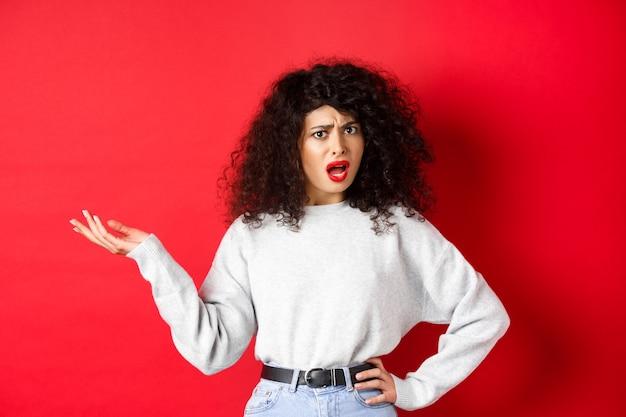 곱슬머리를 한 짜증나고 혼란스러운 백인 여성, 손을 들고 말다툼을 하고, 논쟁을 하고, 무언가를 이해할 수 없고, 빨간 배경에 서 있다