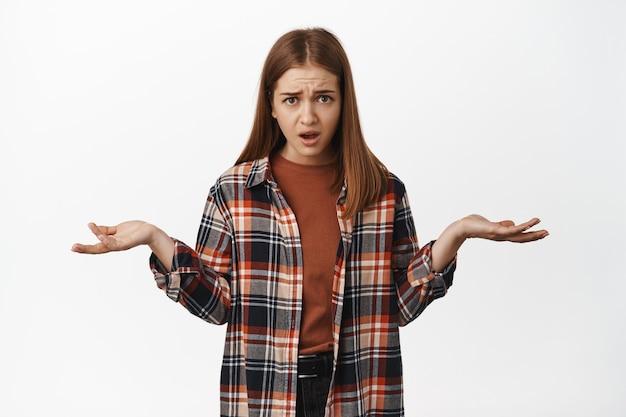 イライラして混乱している女性は、困惑し、肩をすくめ、手を横に広げ、質問されて腹を立てているように見えます。何が起こっているのか、理解できません。
