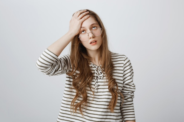 Раздраженная и расстроенная девушка закатила глаза и обеспокоилась фейспалмом