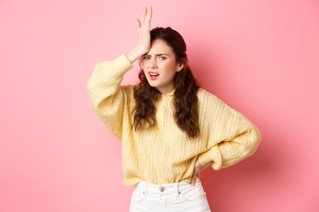 Раздраженная и разочарованная молодая женщина смотрит ладонью, держа руку на лбу и разочарованно смотрит в камеру, стоя у розовой стены
