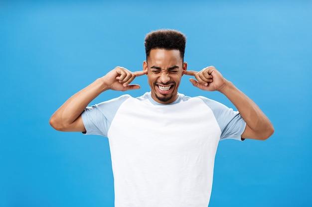 Раздраженный и раздраженный недовольный молодой афроамериканец в модной футболке, закрывающий уши ...