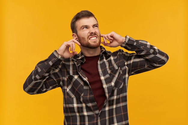 Annoyed angry young man in checkered shirt with beard covered ears by fingers and feels irritated beacause of noise over yellow wall