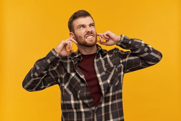 Раздраженный сердитый молодой человек в клетчатой рубашке с пальцами прикрыл бородой уши и чувствует раздражение из-за шума над желтой стеной