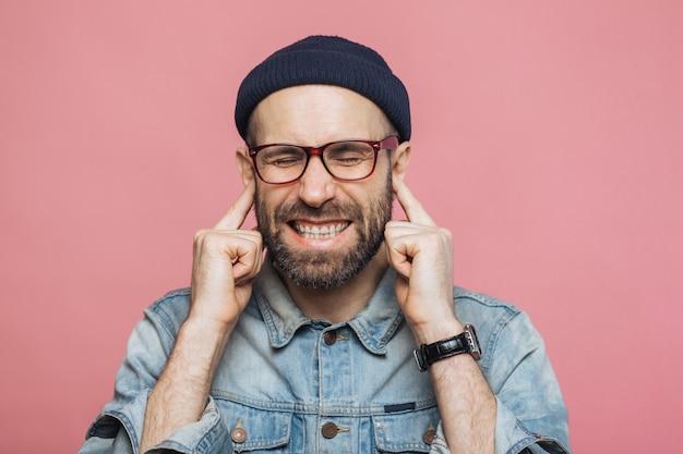 Annoyed bearded male plugs ears as hears unpleasant sound, keeps eyes shut