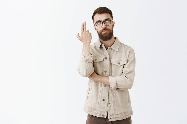 Раздраженный бородатый мужчина в очках позирует у белой стены