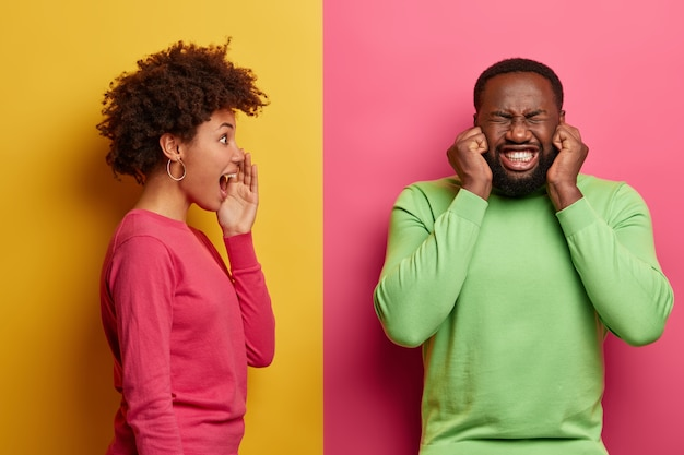 Annoyed bearded man plugs ears, clenches teeth, doesnt want to hear wife shouting, wears green jumper. african american woman keeps palm near mouth, screams and looks at husband, stands in profile
