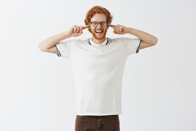 Ragazzo barbuto infastidito rossa in posa contro il muro bianco con gli occhiali