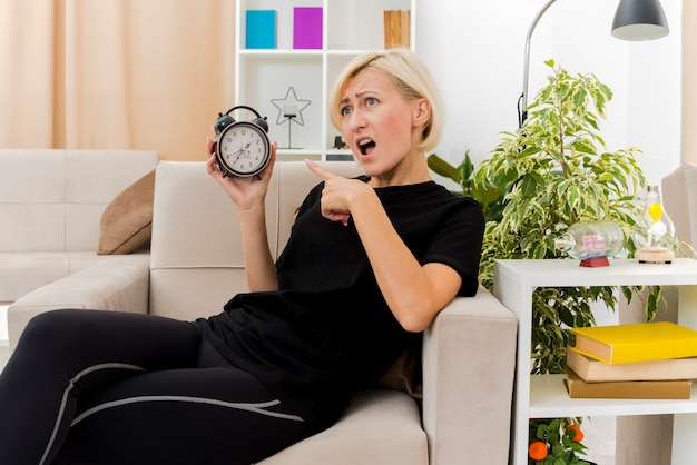 Infastidita bella donna russa bionda sdraiata sulla poltrona tenendo e indicando la sveglia all'interno del soggiorno
