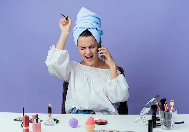 イライラした美しい女の子に包まれたヘアタオルは、紫色の壁に隔離された電話で話しているリップグロスを保持している化粧ツールの叫びとテーブルに座っています