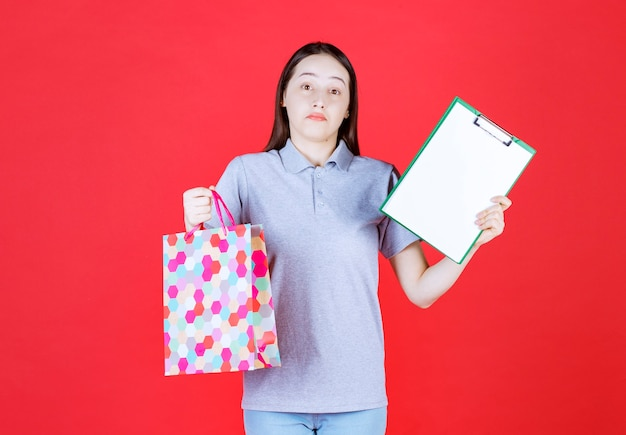 Annoyed beautiful lady holding shopping bag and clipboard