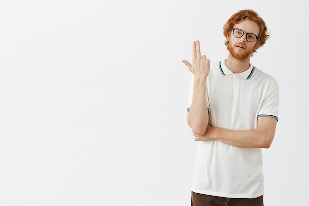 Ragazzo rosso barbuto infastidito o annoiato in posa contro il muro bianco con gli occhiali