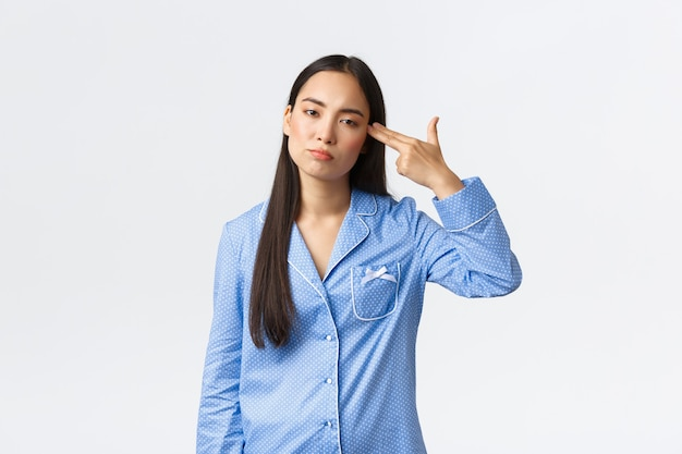 Annoyed and bothered asian girl in blue pajamas looking with reluctant, shooting herself with gun gesture as feeling fed up, tired of hearing or seeing something boring or dumb, white background.