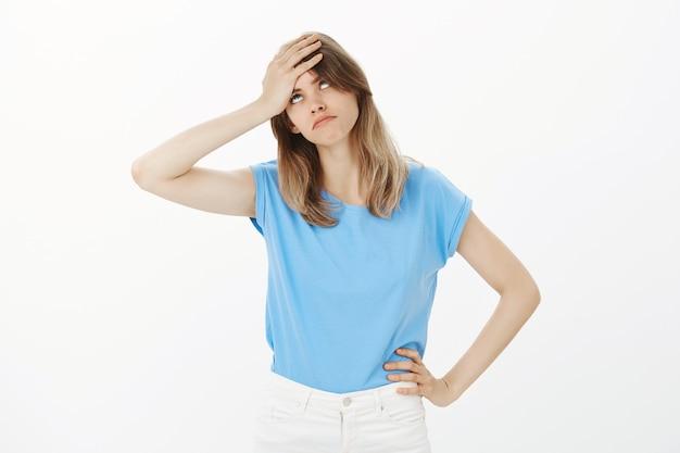 Donna bionda infastidita e infastidita alza gli occhi e schiaffeggia la fronte turbata, sembra irritata