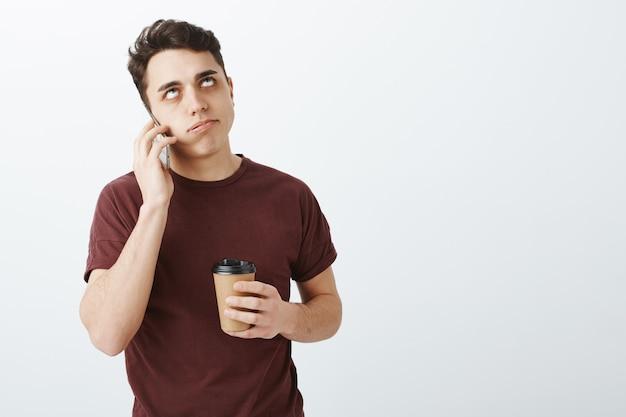Uomo bello infastidito infastidito con i capelli scuri corti che parla dal telefono
