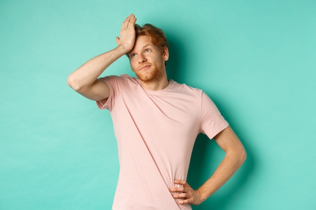 Annoyed and bothered redhead male model showing facepalm and roll eyes, standing over mint background. copy space
