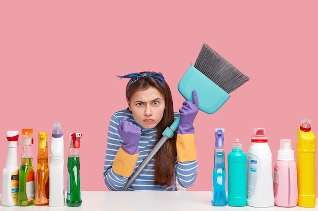 Annoyed brunette woman shows fist with anger, carries blue broom, wears casual clothes, uses chemical supplies for cleaning house
